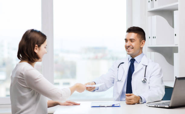 smiling doctor and young woman meeting at hospital stock photo