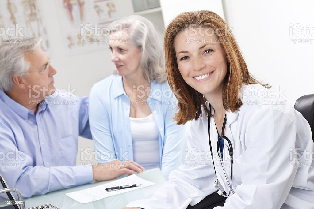 Smiling Doctor at Desk Meeting With Senior Adult Couple royalty-free stock photo