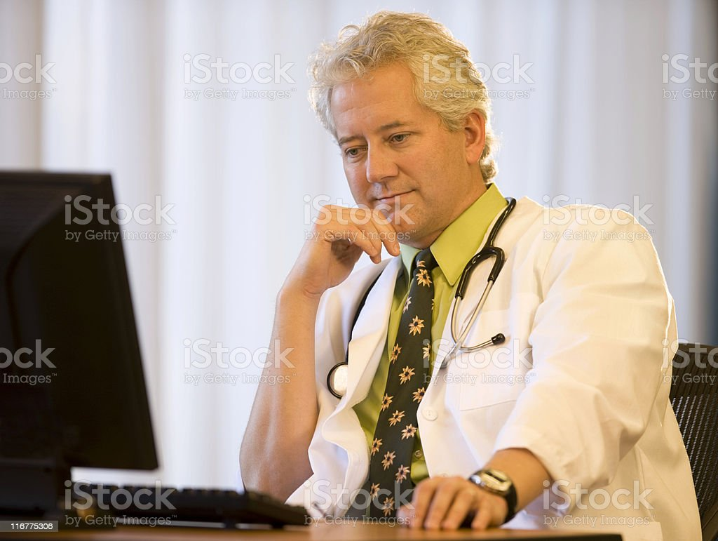 Smiling Doctor At His Desk royalty-free stock photo
