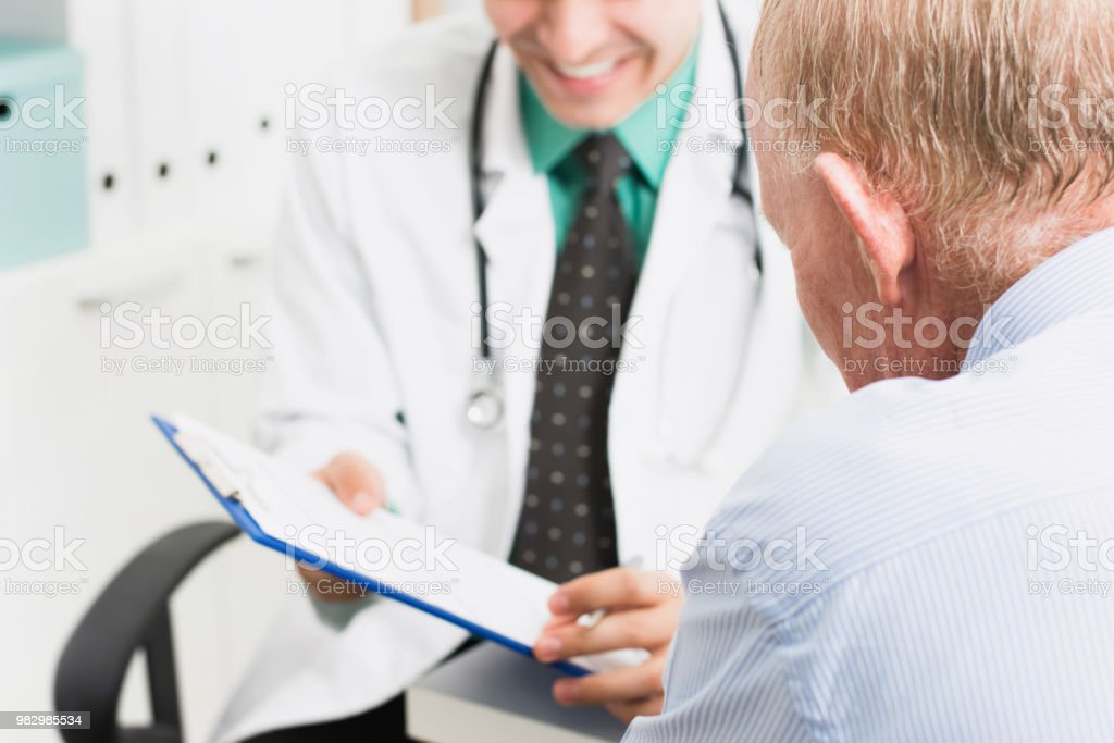Smiling doctor consulting with senior male patient stock photo