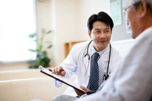 Smiling doctor discussing over medical record with senior man in hospital