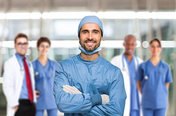sorrindo médico na frente de sua equipe - cirurgião - fotografias e filmes do acervo