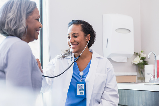 A mid adult female doctor smiles confidently as she listens to a senior female patient's heart during an annual medical exam.