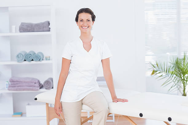 smiling doctor looking at camera sitting on massage table - massage therapist stock pictures, royalty-free photos & images