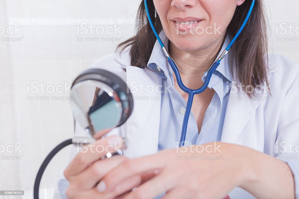 Smiling doctor looking at manometer stock photo