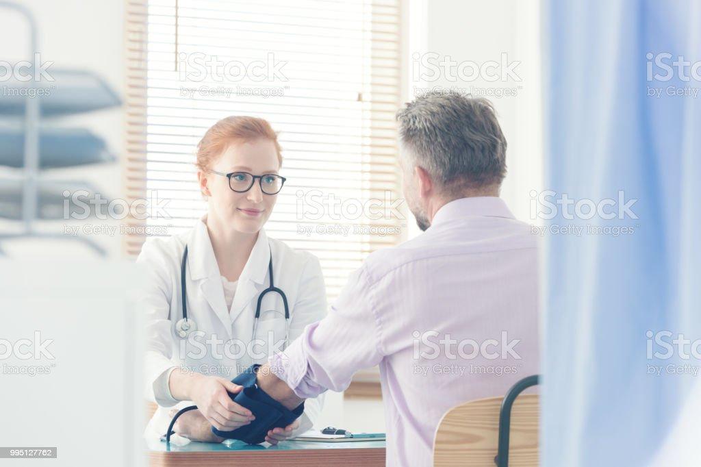 Lächelnd Arzt messen Patient Druck – Foto