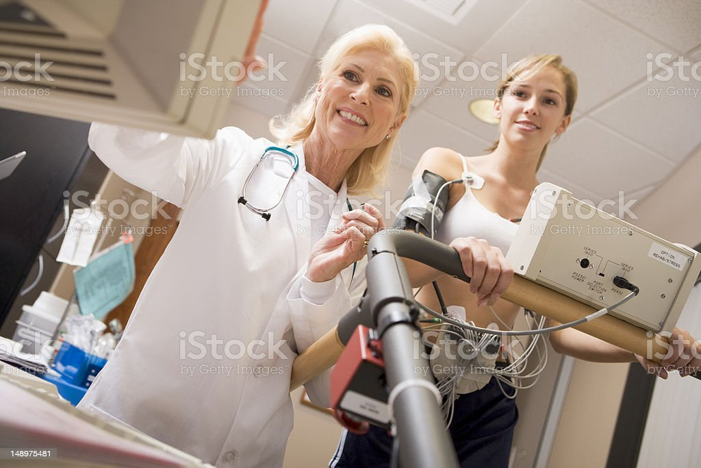 Smiling doctor monitoring patient's vitals on a treadmill stock photo