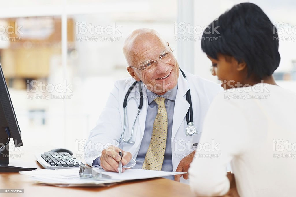 Smiling doctor showing medical reports to his patient stock photo