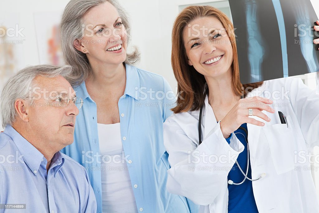 Smiling Doctor Showing X-Ray Results to Mature Adult Couple royalty-free stock photo