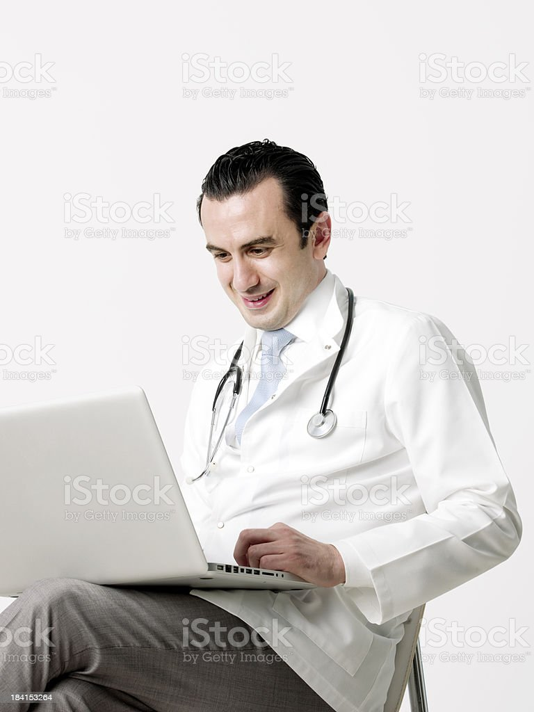 Smiling doctor sitting in front of a computer royalty-free stock photo