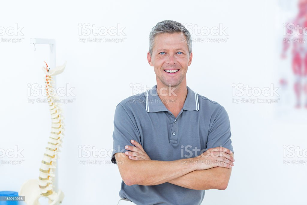 Smiling doctor standing arms crossed stock photo