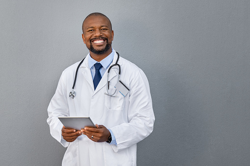 African american doctor holding digital tablet against grey background. Smiling mature doctor in labcoat standing against gray background. Successful happy healthcare worker looking at camera, copy space.