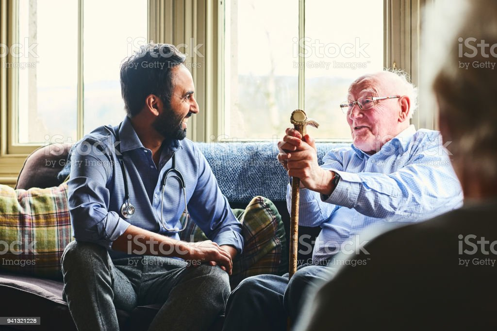 Smiling doctor visiting senior man at home stock photo