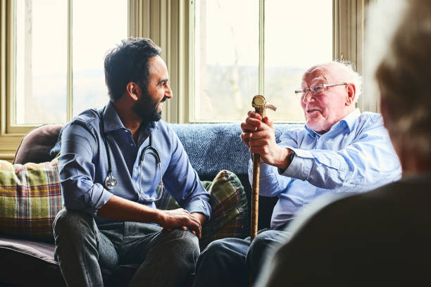 smiling doctor visiting senior man at home - geriatrics stock pictures, royalty-free photos & images