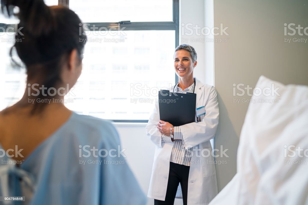 Smiling doctor with clipboard looking at patient stock photo