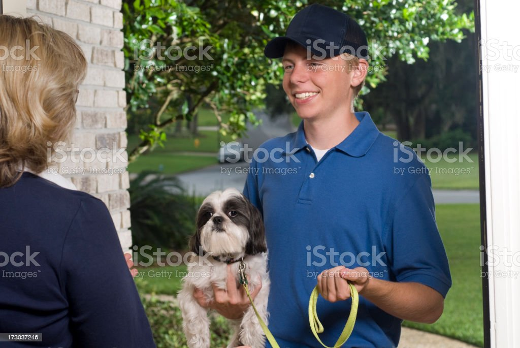 Smiling dog walker dropping off a dog to its female owner royalty-free stock photo