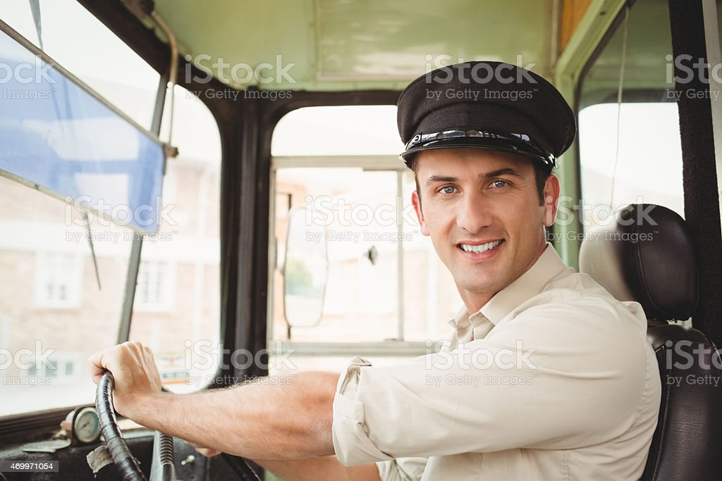 Smiling driver driving the school bus stock photo