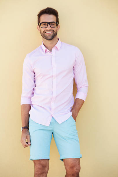 Smiling dude in pink Smiling dude in pink shirt and shorts, portrait shorts stock pictures, royalty-free photos & images