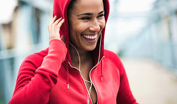 Smiling during workout Portrait of young woman listening to music during workout tuff stock pictures, royalty-free photos & images