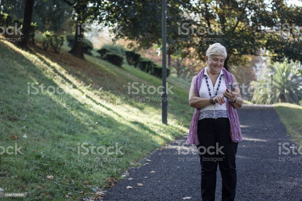 Blonde senior woman dialing touch screen smart phone outdoors....