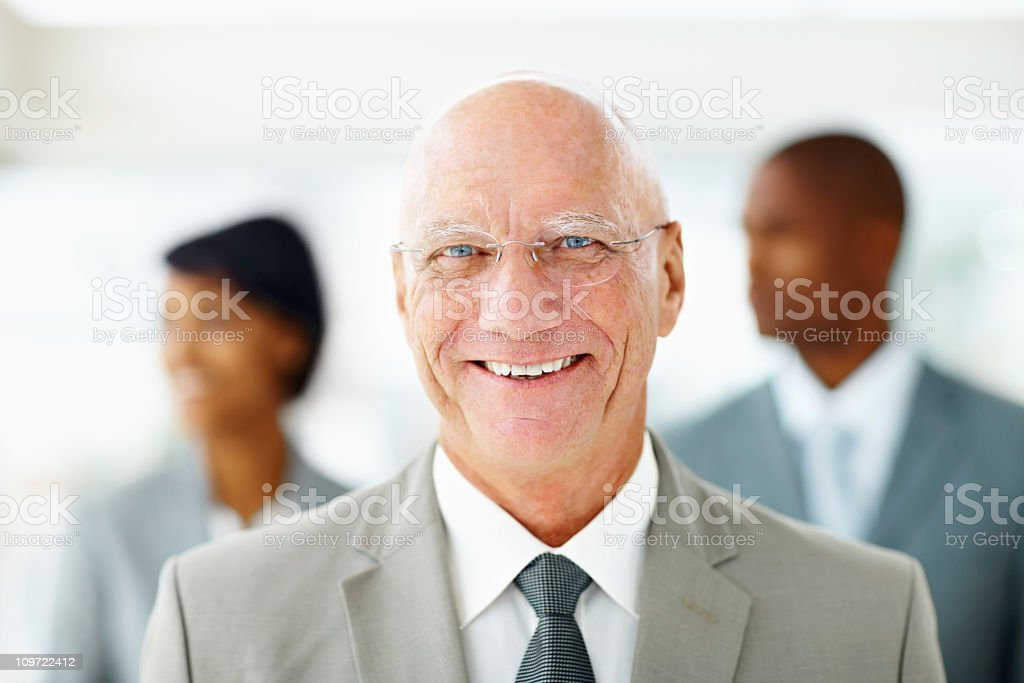 Smiling elderly business man with his blur colleague at back royalty-free stock photo