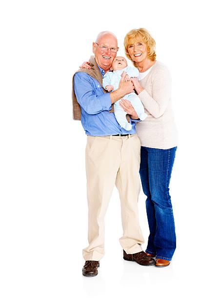 Pareja sonriendo de edad avanzada con su nieto de pie juntos - foto de stock