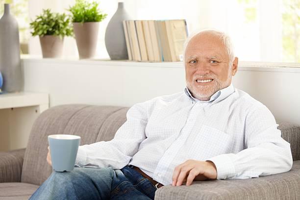 Smiling elderly man having coffee on sofa stock photo