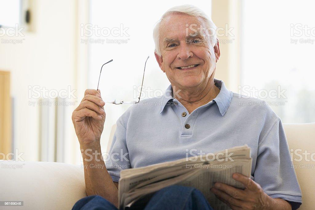 Smiling Elderly man in the living room reading newspaper stock photo