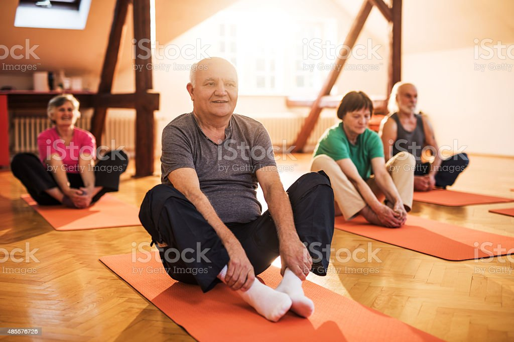 Smiling elderly people doing stretching exercises on a training class. stock photo
