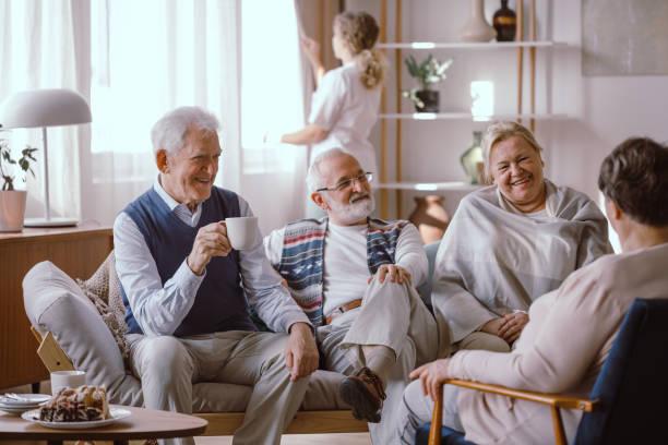 Smiling elderly people talking together in nursing home stock photo