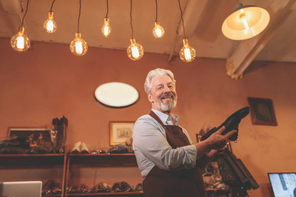 Smiling elderly shoemaker with a shoe stock photo