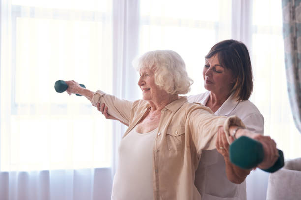 Smiling elderly woman and her nurse exercising with dumbbells stock photo