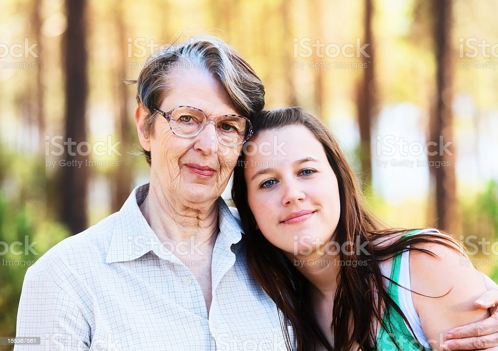 Smiling elderly woman embraces happy young girl affectionately stock photo