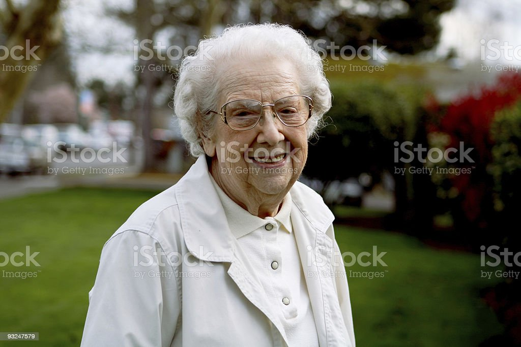 Smiling elderly woman outdoors dressed in white royalty-free stock photo