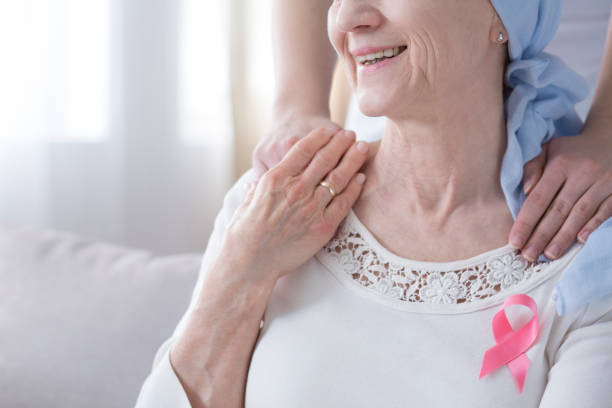 Smiling elderly woman with cancer Close-up of smiling elderly woman with pink ribbon as symbol of fight against breast cancer chemotherapy cancer stock pictures, royalty-free photos & images