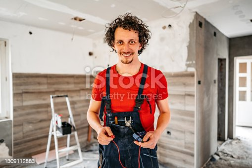Portrait of young handsome smiling electrician renovating house. Holding electrical measuring instrument.