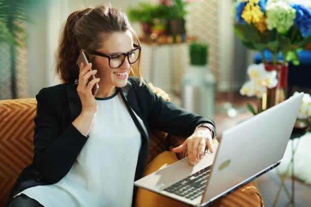 smiling elegant female with laptop using mobile phone stock photo