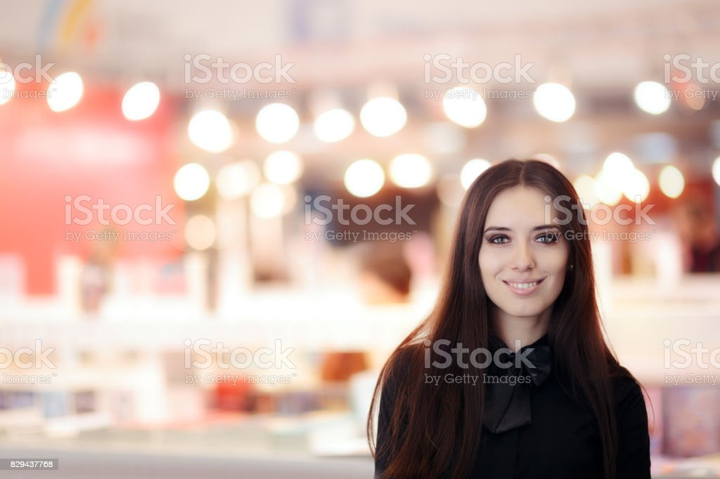 Sonriente a mujer elegante vestida con camisa negra y pajarita de pie en el interior - foto de stock