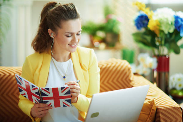 smiling elegant woman with laptop taking notes in notebook stock photo