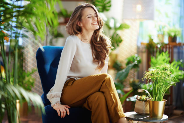 smiling elegant woman with long wavy hair at home in sunny day stock photo