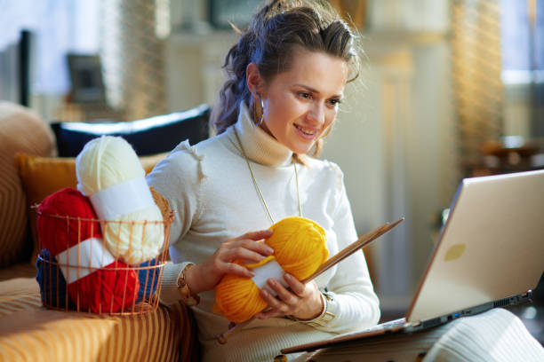smiling elegant woman with yarn learn how to knit stock photo