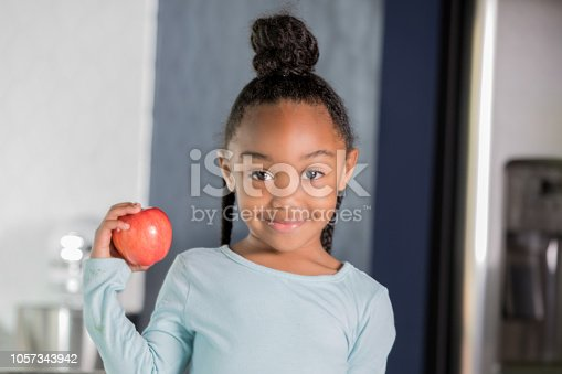 Adorable African American little girl is smiling and looking a the camera. Child is holding a red apple and making healthy food choices at home in a modern kitchen.