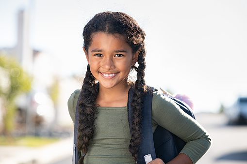 Portrait of happy indian girl with school bag standing outdoor. Little happy schoolgirl going to school, back to school and education concept. Beautiful cute mixed race female student smiling and looking at camera.
