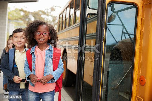 1031397608 istock photo Smiling elementary school kids queueing for the school bus 1031397104