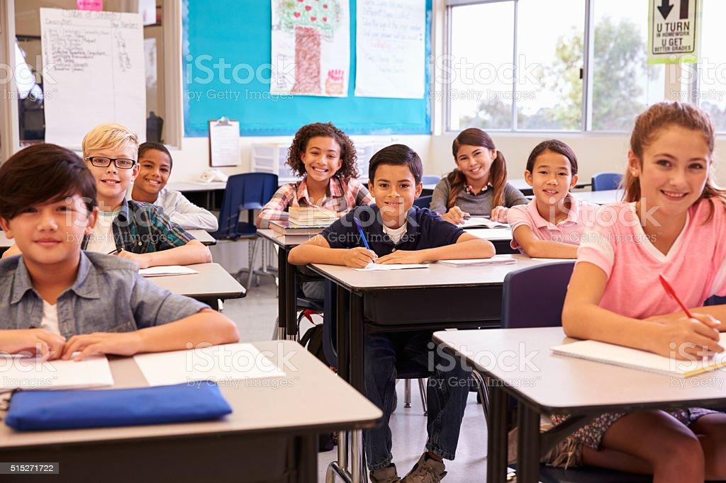 Scrivania Per Bambini Elementari : Scuola elementare sorridente bambino seduto alla scrivania in aula