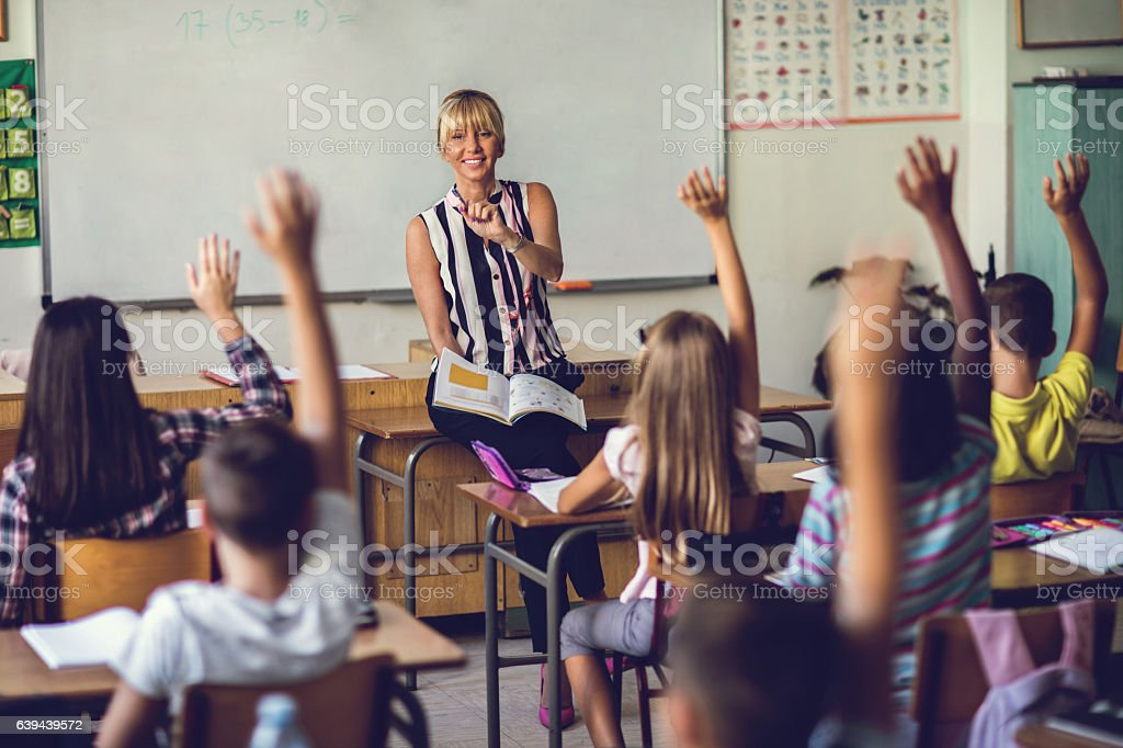 Smiling elementary school teacher asking the question in the classroom. - Photo