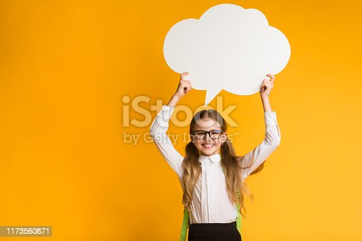 Smiling Elementary Student Girl Holding Speech Bubble Overhead On Yellow Studio Background. Thinking Of School. Mockup, Free Space