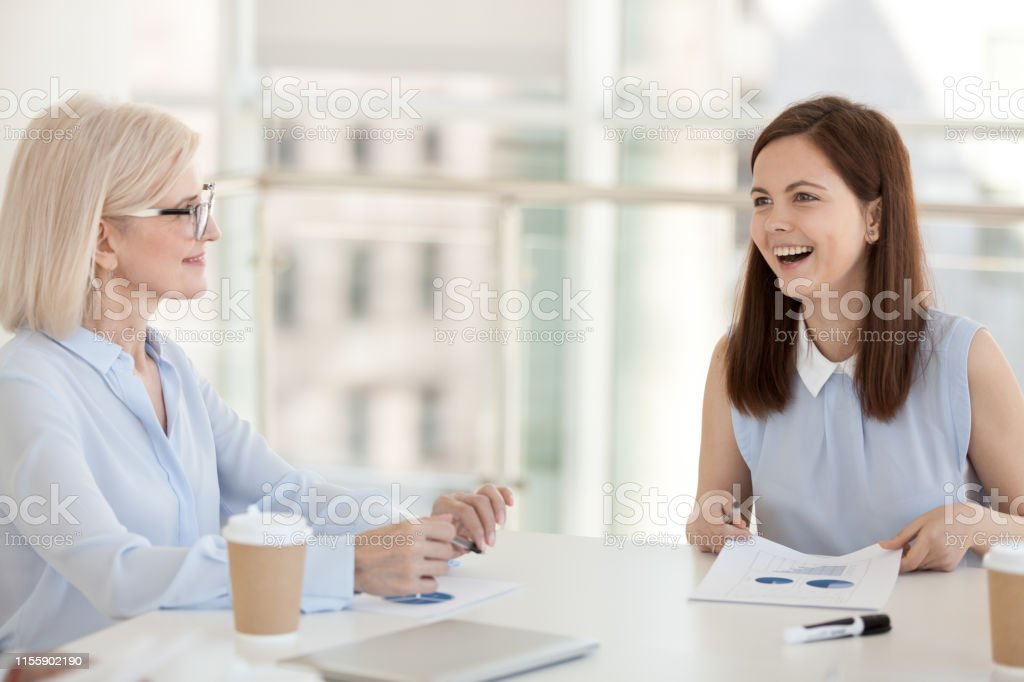 Smiling employees discuss paperwork statistics, project result at...