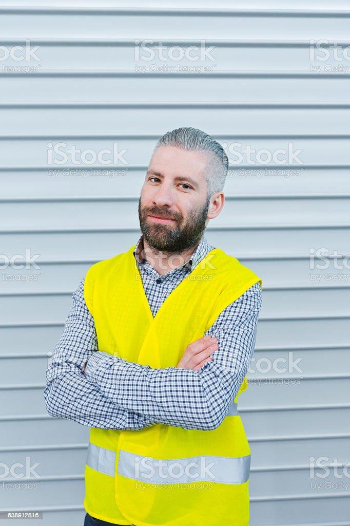 Smiling engineer in front of metal door Engineer standing outdoors in front of metal door, smiling at camera. Adult Stock Photo