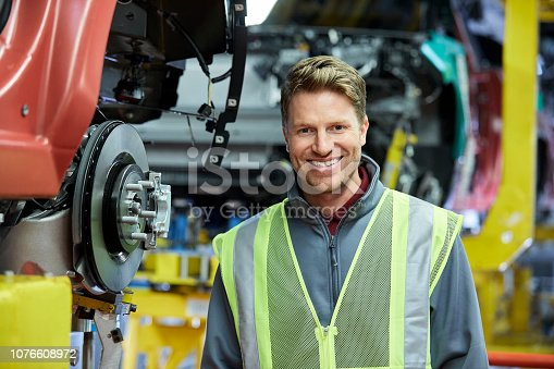 941796726istockphoto Smiling engineer standing against production line 1076608972